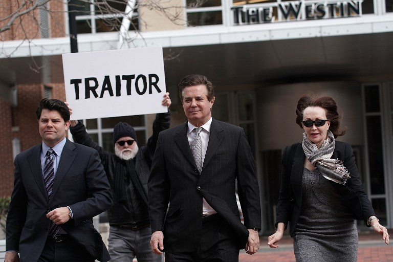 ALEXANDRIA, VA - MARCH 08: Former Trump campaign manager Paul Manafort (2nd R) arrives with his wife Kathleen Manafort (R) at the Albert V. Bryan U.S. Courthouse for an arraignment hearing as a protester holds up a sign March 8, 2018 in Alexandria, Virginia. Manafort was scheduled to enter a plea on new tax and fraud charges, brought by special counsel Robert Mueller's Russian interference investigation team, at the Alexandria federal court in Virginia, where he resides.   Alex Wong/Getty Images/AFP
