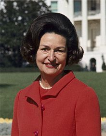 220px-Lady_Bird_Johnson,_photo_portrait,_standing_at_rear_of_White_House,_color,_crop