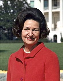 220px-Lady_Bird_Johnson_photo_portrait_standing_at_rear_of_White_House_color_crop