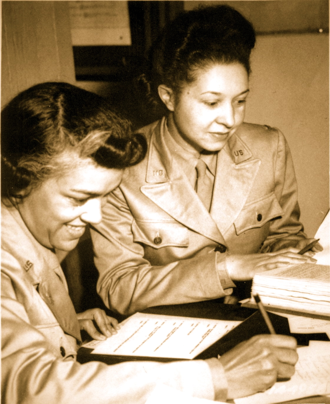 7-WAAC's at work in Temp. Bldg. 'M', 26th Street, Washington, DC Headquarter. Left to right; Lts. Harriet West and Irma Cayton, doing their recruiting schedule report in 1942 (c. National Archive)