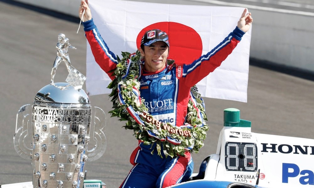 May 29, 2017; Indianapolis, IN, USA; Verizon IndyCar Series driver Takuma Sato holds up a Japanese flag after winning the 101st Running of the Indianapolis 500 at the Indianapolis Motor Speedway. Mandatory Credit: Brian Spurlock-USA TODAY Sports