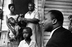3-Dr. Martin Luther King Jr., right, chats with Greenwood, Mississippi African Americans on their front porch